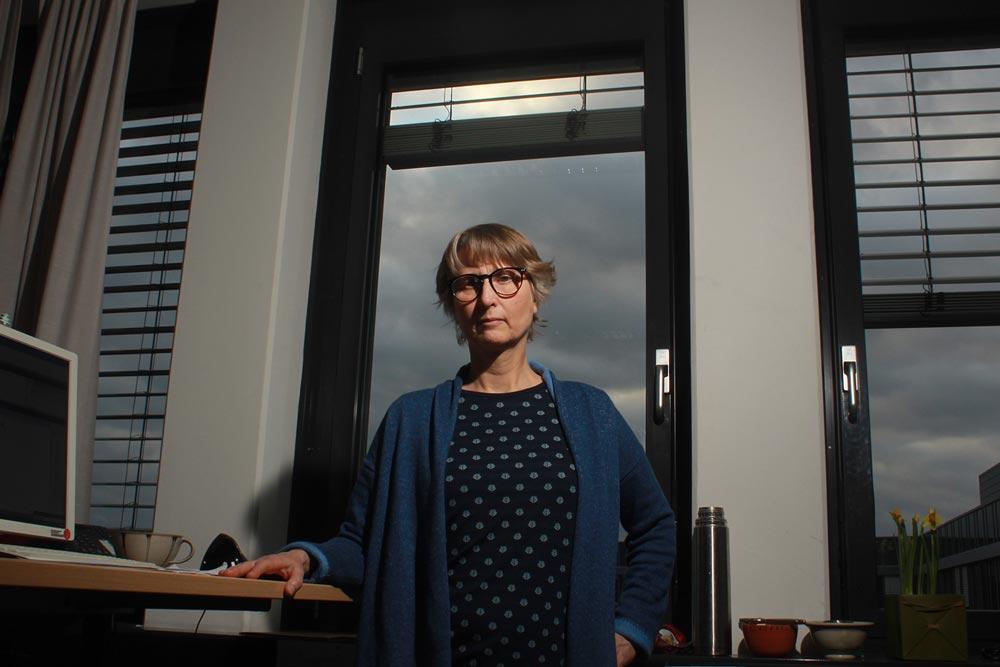 Eine IT Mitarbeiterin der DRV Bund steht in einem Büro eines Dienstgebäudes.
