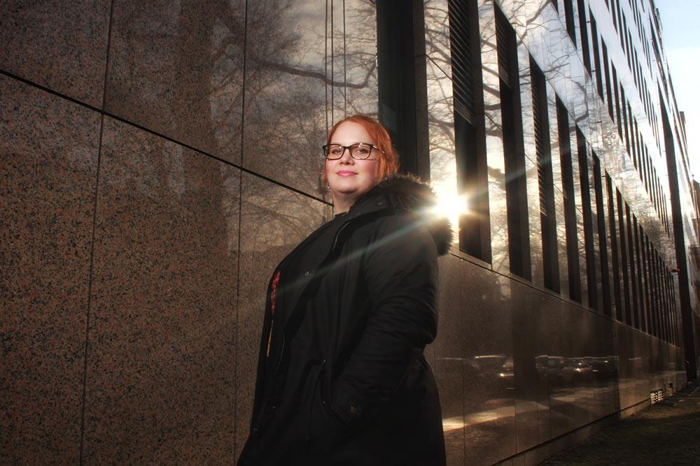 Eine IT Mitarbeiterin der DRV Bund steht vor einem Dienstgebäude der DRV Bund.